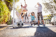 Friends playing soccer on sunny urban summer street - CAIF04242