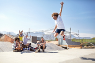 Friends watching and cheering man jumping in roller skates at sunny skate park - CAIF04245