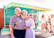 Portrait smiling senior business owners outside sunny food cart - CAIF04251