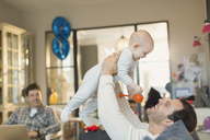 Male gay parents playing with baby son in living room - CAIF04290