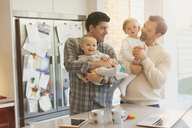 Male gay parents holding baby sons in kitchen - CAIF04302