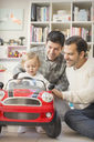 Male gay parents pushing baby son in toy car - CAIF04311