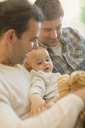 Male gay parents holding baby son - CAIF04317