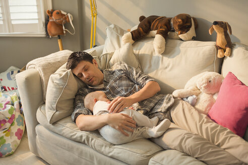 Exhausted father and baby son sleeping on sofa - CAIF04326