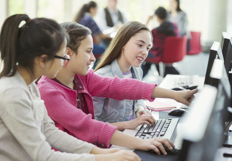 Girl students studying together at computer in library - CAIF04368