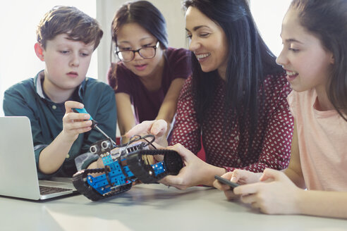 Female teacher and students programming and assembling robotics in classroom - CAIF04410