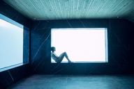 Woman sitting on ledge at window in pool room - CAIF04425
