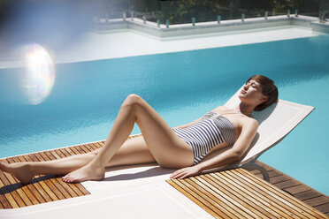 Woman sunbathing on lounge chair at luxury poolside - CAIF04428