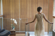 Woman standing at top of stairs in modern house - CAIF04431