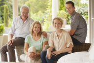 Portrait of smiling couples on patio - CAIF04434