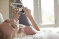Laughing woman laying in bed using digital tablet - CAIF04440
