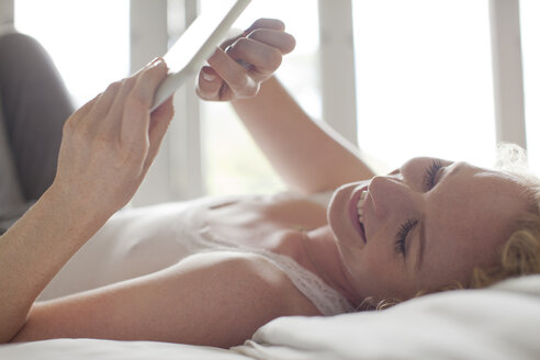 Smiling woman laying in bed and using digital tablet - CAIF04449