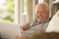 Portrait of smiling senior man using laptop on porch - CAIF04458