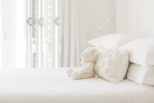 Teddy bear and pillows on white bed - CAIF04464