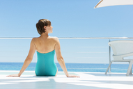 Woman relaxing poolside with ocean in background - CAIF04467