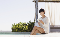 Smiling woman using digital tablet at poolside - CAIF04479