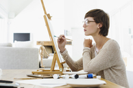 Woman painting on easel at table - CAIF04488