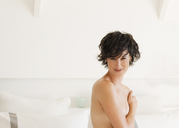 Portrait of smiling woman covering breasts - CAIF04497