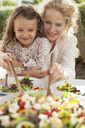 Mother and daughter eating in garden - CAIF04533