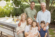 Portrait of smiling multi-generation family at table in garden - CAIF04536