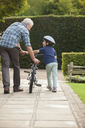 Grandfather and grandson pushing bicycle on sidewalk - CAIF04539