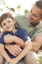Father and son hugging outdoors - CAIF04542