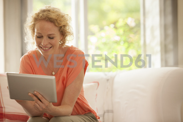 Woman using digital tablet on sofa - CAIF04545