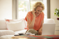Woman talking on cell phone and using laptop in living room - CAIF04551