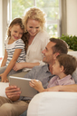 Family using digital tablet on sofa - CAIF04554
