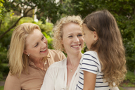 Three generations of women smiling outdoors - CAIF04560