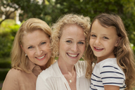 Three generations of women smiling outdoors - CAIF04563
