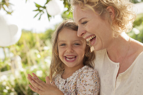 Mother and daughter laughing outdoors - CAIF04569