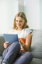 Woman using digital tablet on sofa - CAIF04590