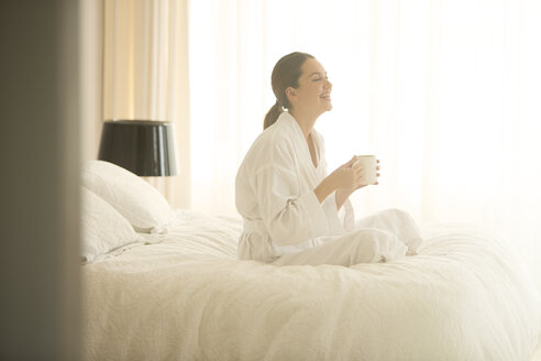 Smiling woman in bathrobe drinking coffee cross-legged on bed - HOXF00219