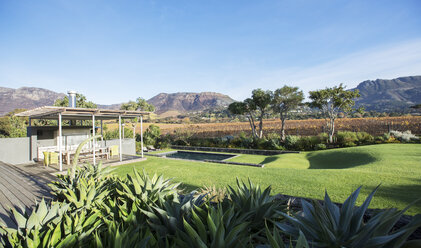 Sunny modern patio and yard with mountains in background - HOXF00228