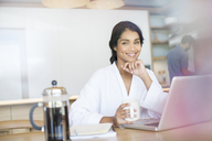 Portrait smiling woman in bathrobe drinking coffee at laptop - HOXF00237