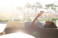Woman laying on chaise lounge using digital tablet on sunny patio - HOXF00240