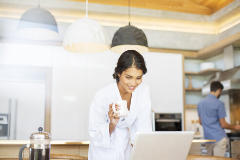 Woman in bathrobe drinking coffee and using laptop in kitchen - HOXF00255