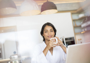 Portrait confident woman in bathrobe drinking coffee at laptop - HOXF00258