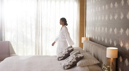 Woman in bathrobe walking in bedroom - HOXF00267