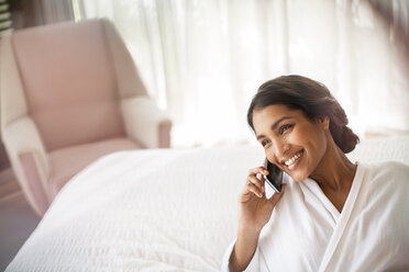 Smiling woman in bathrobe talking on cell phone on bed - HOXF00279