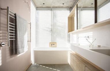 Light shining through blinds behind soaking tub in luxury bathroom - HOXF00282