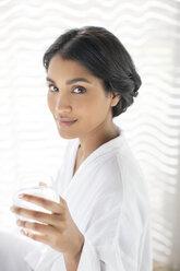 Portrait confident woman in bathrobe drinking water - HOXF00285