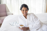 Portrait smiling woman in bathrobe drinking tea on bed - HOXF00288