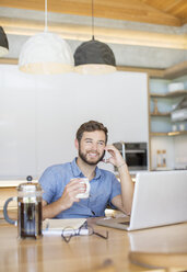 Smiling man drinking coffee and talking on cell phone at laptop - HOXF00309
