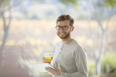 Portrait smiling man drinking orange juice and using digital tablet on patio - HOXF00312