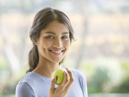 Close up portrait smiling woman eating green apple - HOXF00315