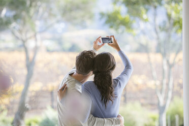 Couple taking selfie with camera phone on patio - HOXF00318