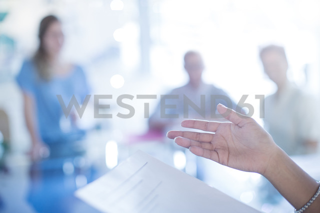 Close up of businesswoman's hand gesturing to paperwork in meeting - HOXF00348