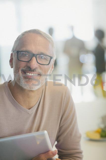 Portrait smiling businessman with digital tablet - HOXF00360